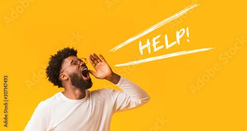 Vászonkép Worried afro guy shouting help over orange background