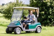 Male Golfer In Golf Cart Showi...