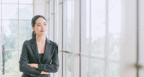 Portrait of smiling pretty young business woman crossed her arms and standing on workplace office and looking out to window.Smile and Thinking for future.