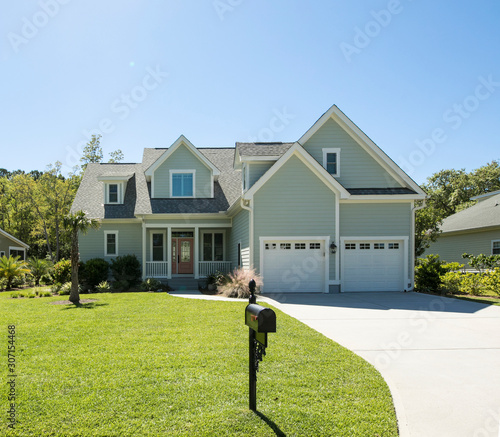 Foto Large beautiful new home on landscaped lot with lawn.