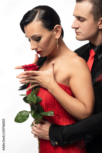 handsome dancer gifting red rose to beautiful partner while performing tango isolated on white
