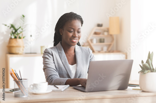 Photo  Smiling afro businesswoman working on laptop in modern office