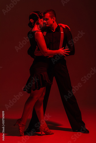 sensual couple of dancers performing tango on dark background with red illuminat Canvas Print