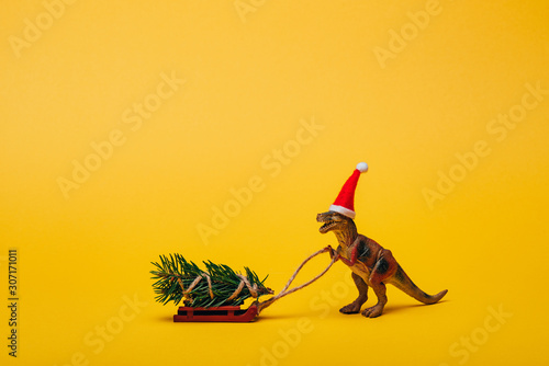 obraz dibond Toy dinosaur in santa hat with pine on sleigh on yellow background