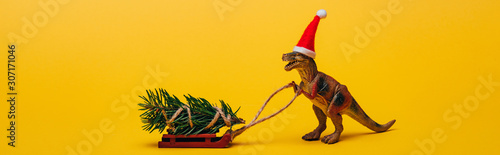 Photo  Panoramic shot of toy dinosaur in santa hat with pine on sleigh on yellow backgr