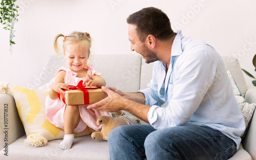 Adorable girl unwrapping gift box from loving father Tablou Canvas