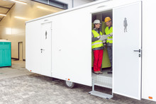 Workers Inspecting A Restroom Trailer Before Renting It Out