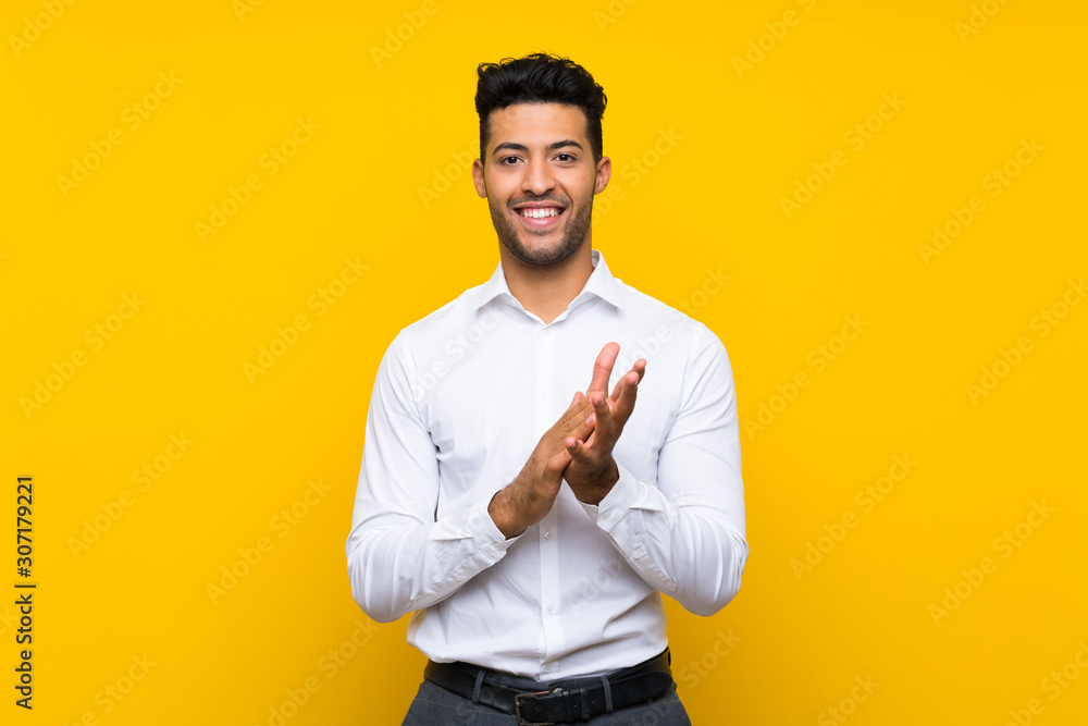 Fototapeta Young handsome man over isolated yellow background applauding