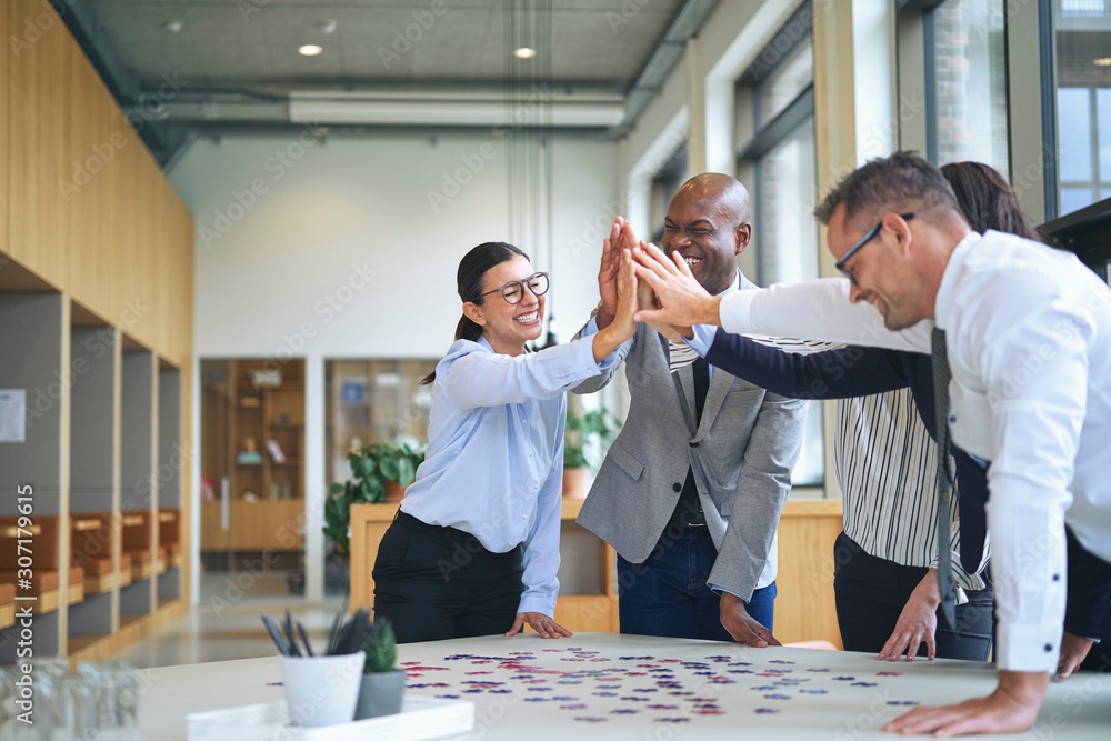 Fototapeta Businesspeople high fiving while solving a puzzle in an office