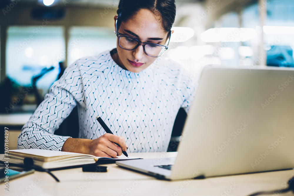 Fototapeta Pensive female administrative manager writing plan for project in notepad sitting at desktop with netbook, concentrated professional secretary assistant concentrated on accounting report in office