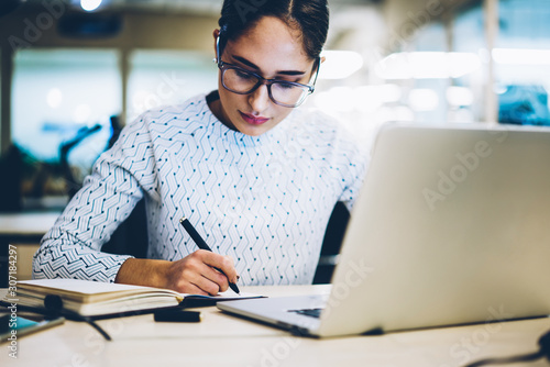 Pensive female administrative manager writing plan for project in notepad sittin Canvas Print