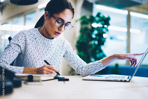 Pensive business woman noting idea for startup planning from web page on laptop computer,professional administrative manager making accountings of income using app on netbook in office interior