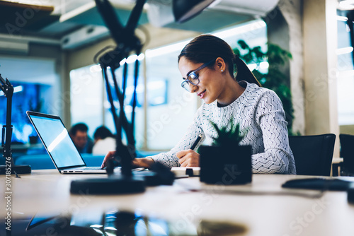Professional female manager writing statement browsing information on laptop com Canvas Print