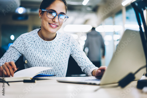 Fototapety, obrazy: Portrait of prosperous business woman in spectacles providing protection while work on laptop computer looking at camera,smiling female manager completing project successfully using netbook in office