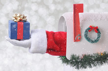 Santa Claus Arm Holding A Small Christmas Present Coming Out Of A Mail Box With Silver Bokeh Background And Snow Effect.
