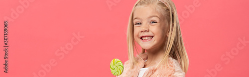 Fototapeta  panoramic shot of smiling and cute kid holding lollipop isolated on pink