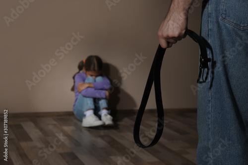 Photo Man threatening his daughter with belt indoors, closeup