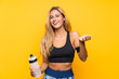 Leinwandbild Motiv Young sport woman with a bottle of water over isolated background