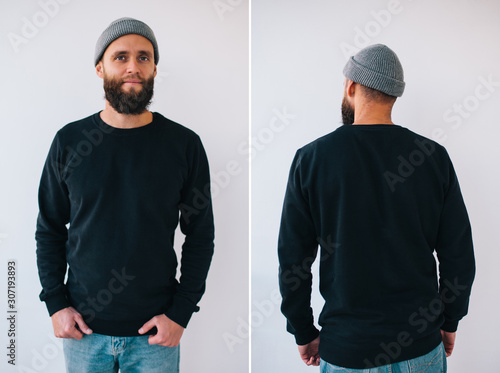 City portrait of handsome hipster guy with beard wearing black blank hoody or sweatshirt with space for your logo or design. Front and back view mockup
