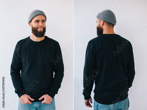 Fotografía  City portrait of handsome hipster guy with beard wearing black blank hoody or sweatshirt with space for your logo or design