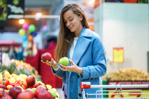 Portrait of attractive woman buyer with cart in the grocery shop during choosing Wallpaper Mural