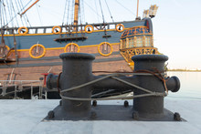 Cast Iron, Black, With Signs Of Corrosion Mooring Device With A Wound Steel Cable Is Fixed To The Concrete Pier Studs And Nuts On The Background Of The Board Of A Wooden Sailing Ship.