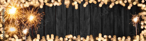 Fototapeta Silvester background banner panorama long- Frame made of sparklers and bokeh lights on rustic wooden texture, with space for text obraz na płótnie