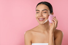 Young Woman Using Facial Cleansing Brush On Pink Background, Space For Text. Washing Accessory