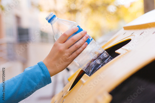 Leinwand Poster Stock photo of a woman's hand recycling a plastic bottle