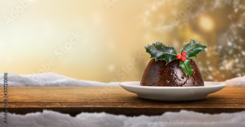 Christmas banner background of a traditional Christmas pudding on the right with a sprig of holly on top with a golden blurred background.