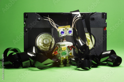 Valokuva  Funny robot-cyborg with VHS video tapes and film on a green background