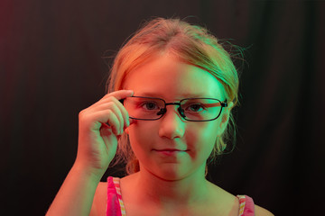 The girl in glasses on a black background holds glasses by the frame.