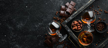 Brandy And Chocolate On A Black Stone Table. Top View. Free Space For Your Text.