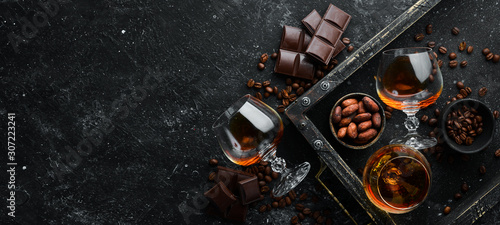 plakat Brandy and chocolate on a black stone table. Top view. Free space for your text.