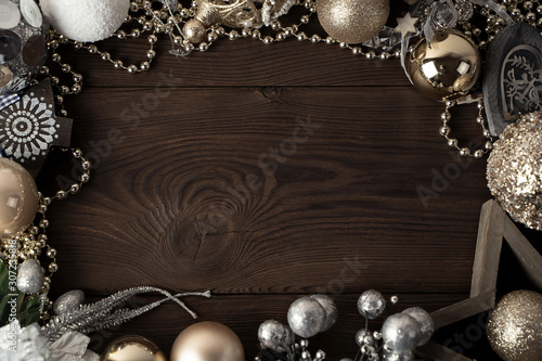 Photo Christmas composition of a wooden star, Christmas gold and silver blinders, wooden heart, branches, gold beads on a brown natural wooden background