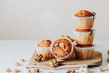 Vanilla Caramel Muffins In Paper Cups On White Wooden Background. Delicious Cupcake With Raisins, Almonds And Nuts. Homemade Biscuit Cakes. Copy Space For Text.