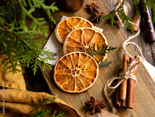 Photo dried orange slices on wooden board with anise stars, cinnamon sticks
