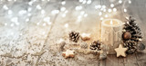 White Christmas candle on rustic wooden boards -  Decoration with natural elements, twigs, pine cones and cookies  -  Advent banner, panorama with magic bokeh lihgts