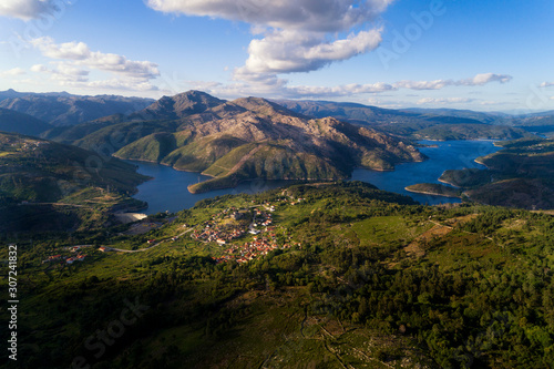 Fototapeta Aerial panoramic view of the historic village of Lindoso, with the surroundings mountains and lake, at the Peneda Geres National Park, in Portugal