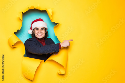 Young man in santa hat pointed with hands on copy space through yellow paper hole Canvas Print