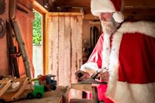 Man Wearing Santa Claus Costume Standing In A Workshop, Building Wooden Toy Car.