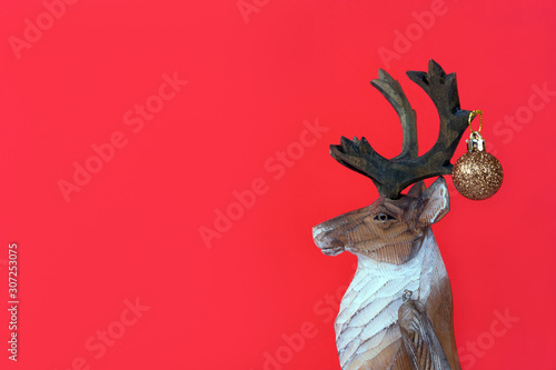 Funny Christmas wood reindeer with small festive ball on a red background. Minimalism holiday concept. New year toy