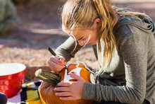 A Teenage Girl Carving Pumpkin...