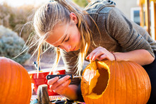 Teenage Girl Carving Pumpkin For Halloween Outdoors