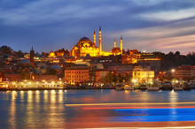 Night View At Yeni Cami Mosque Worship Place From Galata Bridge Reflected In Water Of Golden Horn Of Bosporus.