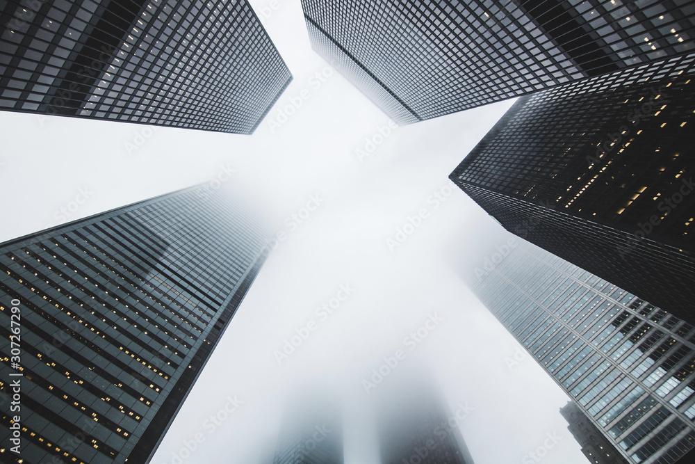 Fototapeta Looking up at sky between high skyscraper towers or tall buildings through skyline fog