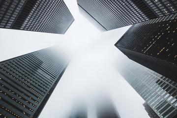 Looking up at sky between high skyscraper towers or tall buildings through skyline fog