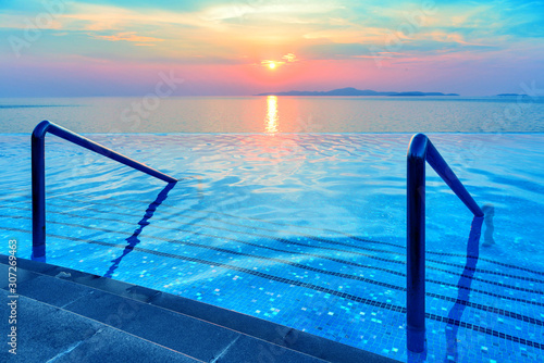 Obraz Swimming pool with stair and sunset background - fototapety do salonu