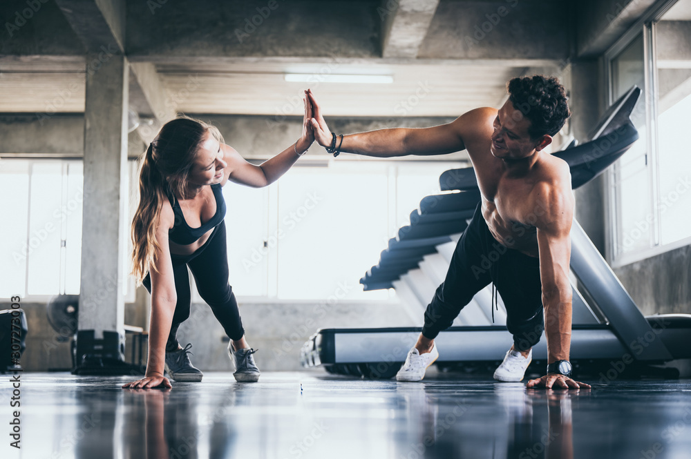 Fototapeta Personal trainer helping woman exercising in the sport gym, training workout in fitness, body healthy sport lifestyle