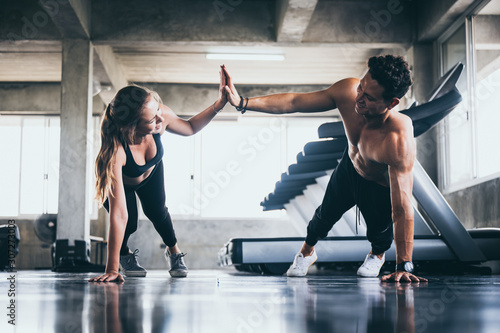 Fototapeta Personal trainer helping woman exercising in the sport gym obraz
